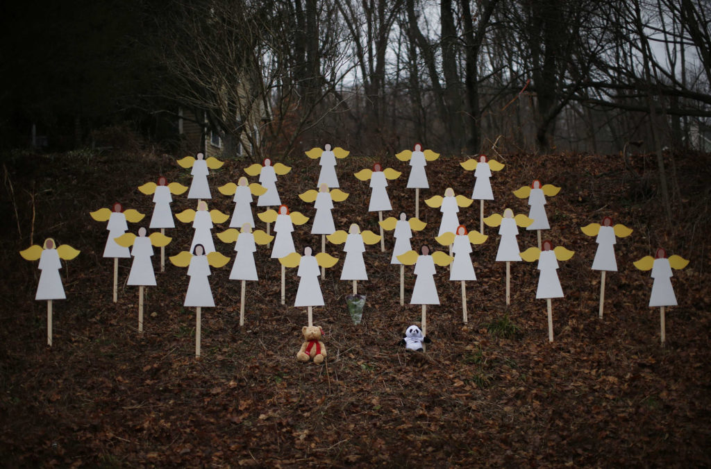 Twenty-seven wooden painted angels created by Eric Mueller are displayed outside his home in Newtown, Conn., Dec. 16. Twelve girls, eight boys and six adult women were killed by a gunman who forced his way into Newtown's Sandy Hook Elementary School Dec. 14. (CNS photos/Mike Segar, Reuters) (Dec. 16, 2012)